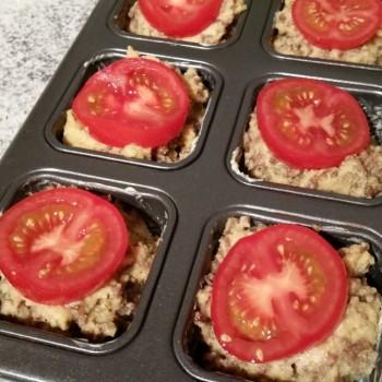 Die Tomaten in dicke Scheiben schneiden und die Küchlein damit belegen.